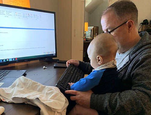 Man with glasses at a desk with a baby on his lap looking like the baby is learning how to use the computer