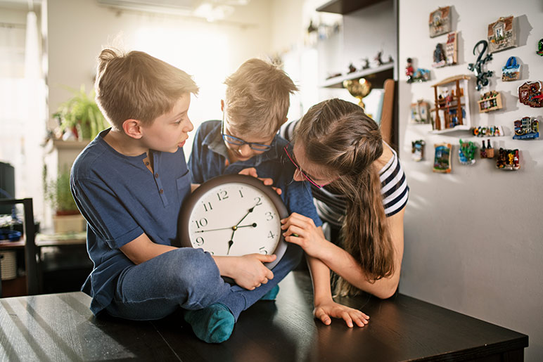 3 kids with a clock - daylight saving time