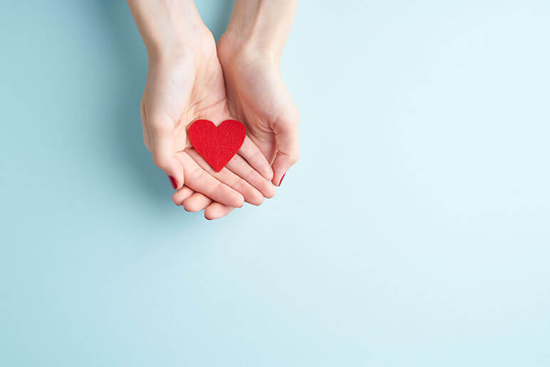 Two hands holding a red heart that have a light blue background
