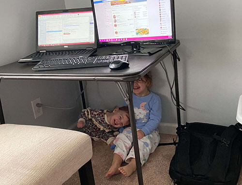 Two smiling children underneath table hiding from their mom who is working from home