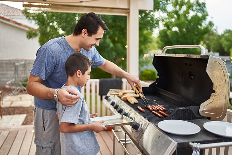 Dad and Son Grilling Hot Dogs