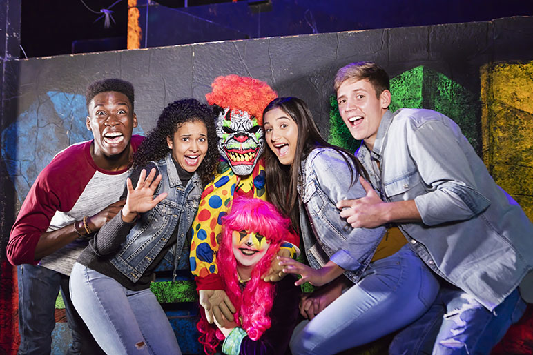 Four teenagers posing for a photo at a haunted house with a scary clown and doll