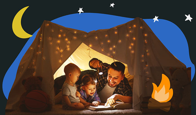 Dad with two young children inside a tent reading a book with a flashlight pointed at the book