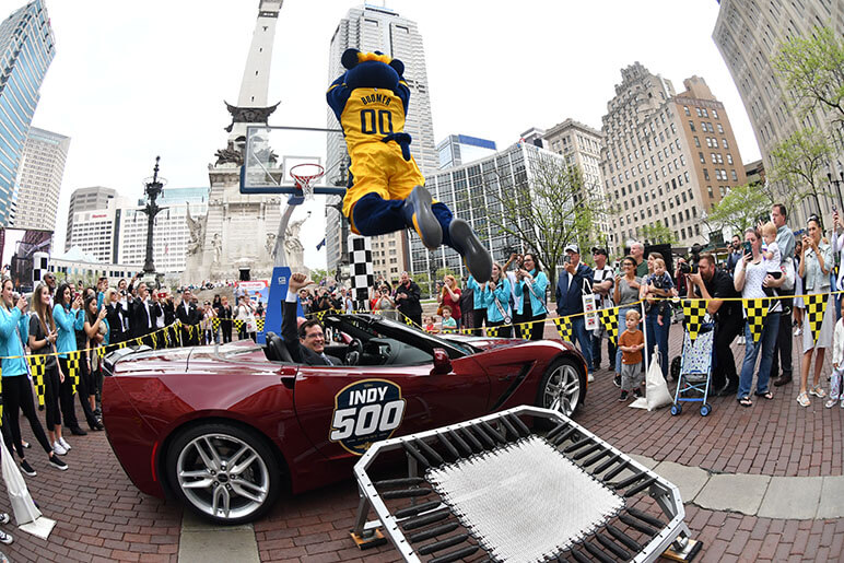 The Pacer's mascot Boomer dunking a basketball over a red car that says Indy 500 on the side in downtown, Indianapolis