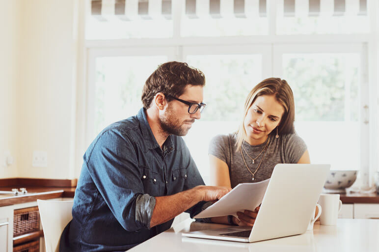 Husband and wife using laptop - checking the premium change on insurance policy