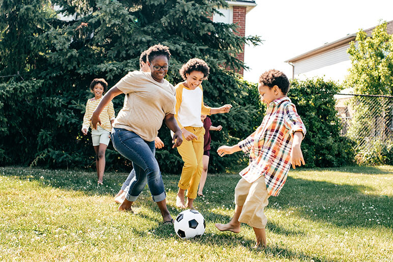 Family of six playing soccer in the backyard on grass