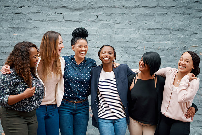 A group of 6 women laughing and smiling