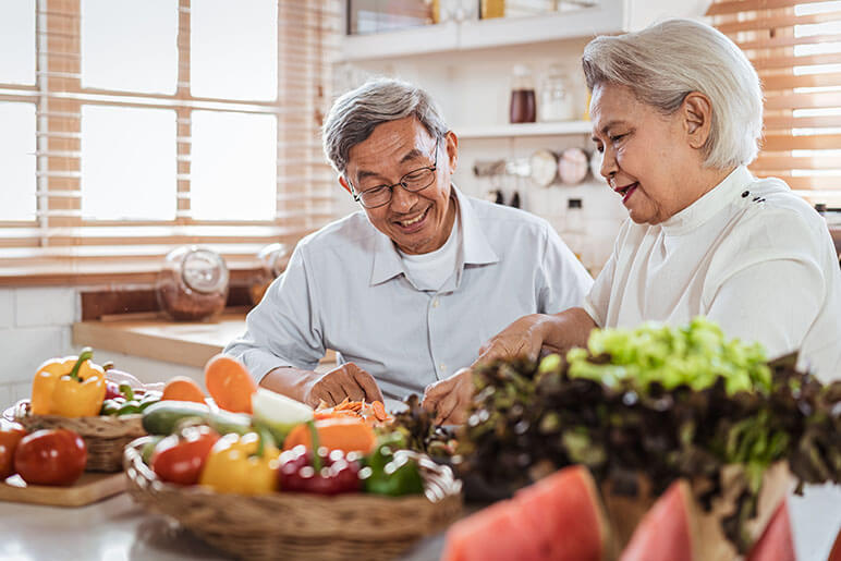 Older couple cutting food and making a meal with each other in the kitchen