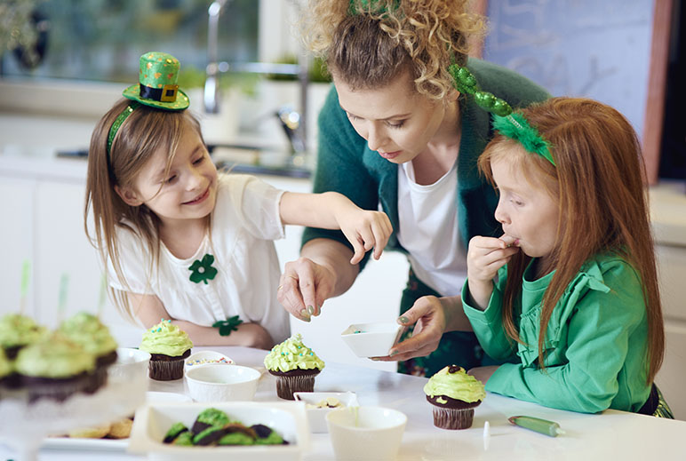 Mom with two daughters making St. Patrick's Day cupcakes while they are wearing green accessories