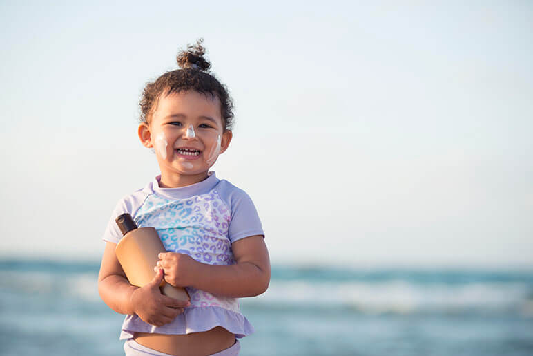 Little girl wearing sunscreen and holding a bottle of sunscreen