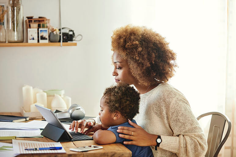 Mother and son sitting at a kitchen table looking at the women's tablet doing work