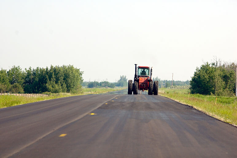 Farm tractor on the right side of the road in an open road with rural areas around it