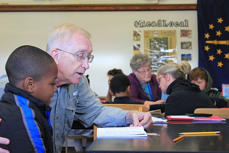 Older man helping child read at a school desk in a school